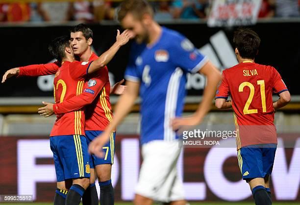 Spain's forward Alvaro Morata celebrates with teammates forward Nolito and midfielder David Silva after scoring a goal during the WC 2018 football...