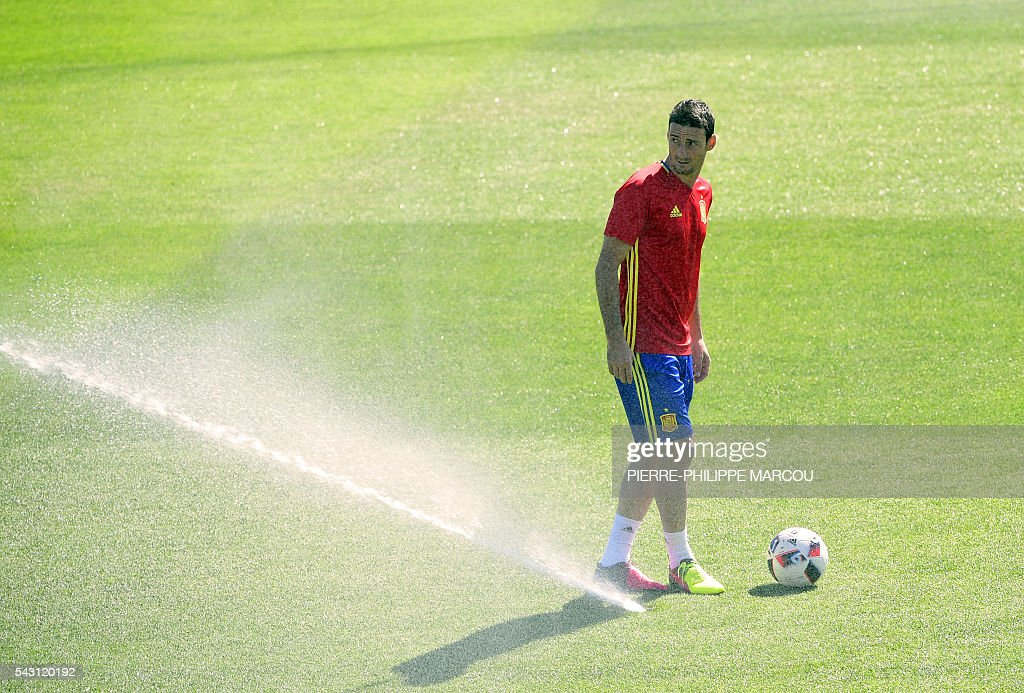 Spain's forward Aritz Aduriz stands next to a sprinkler as he attends a training session at Saint Martin de Re's stadium on June 26, 2016, on the eve of their match against Italy during the Euro 2016 football tournament. / AFP / PIERRE