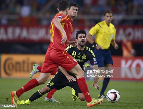 Spain's Forward Diego Costa falls as he vies with Macedonia's Defender Kire Ristevski during the Euro 2016 Group C qualifying football match between...