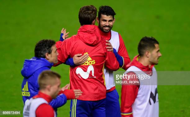 Spain's forward Diego Costa hugs teammate defender Sergio Ramos during a training session at the Molinon stadium in Gijon on March 23 2017 on the eve...