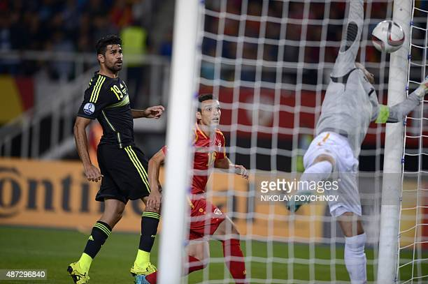 Spain's Forward Diego Costa looks at the ball as Spain's Midfielder Juan Mata scores during the Euro 2016 Group C qualifying football match between...