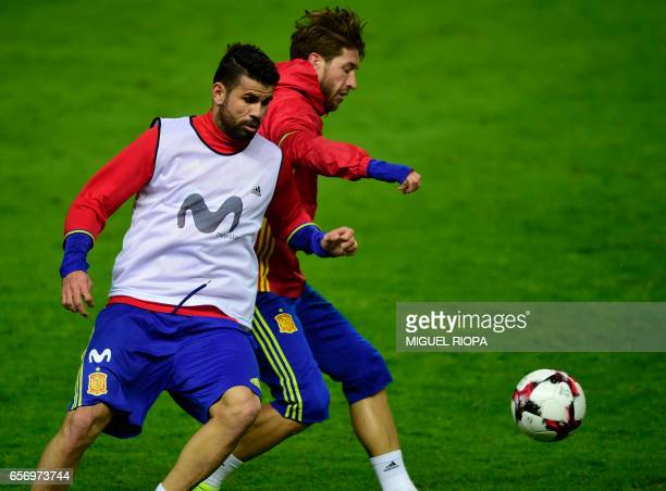 Spain's forward Diego Costa vies with defender Sergio Ramos during a training session at the Molinon stadium in Gijon on March 23 2017 on the eve of...