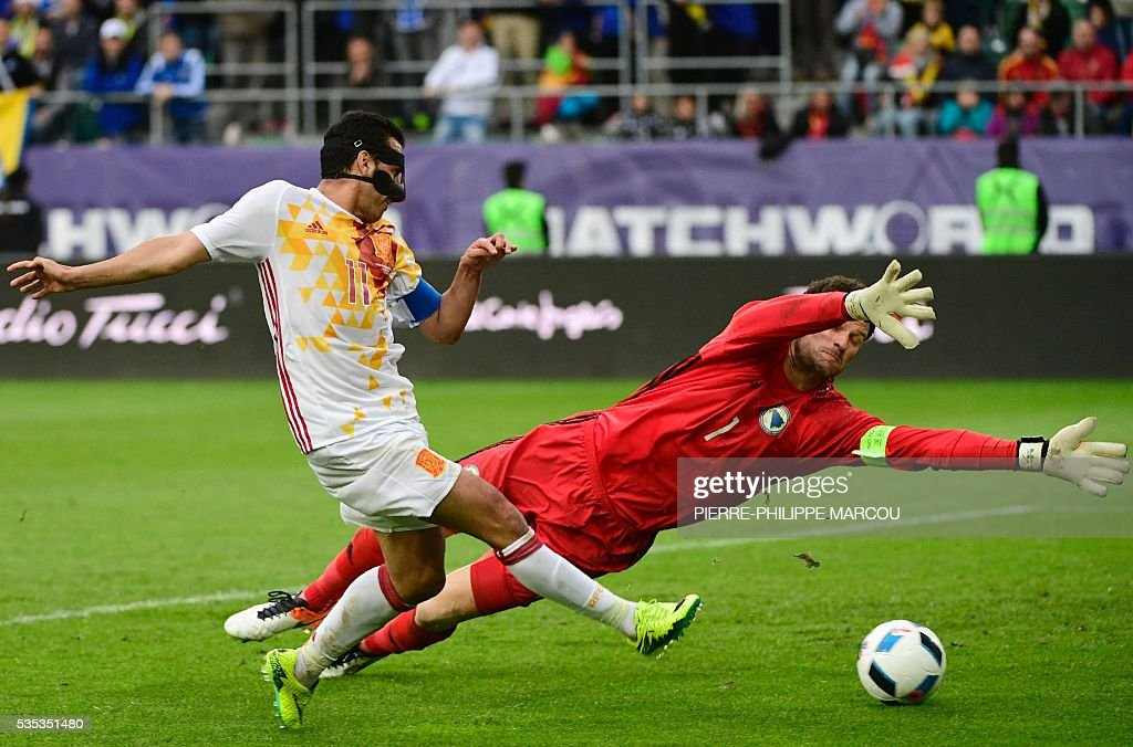 Spain's forward Pedro (L) kicks the ball to score despite the oposition of Bosnia's goalkeeper Asmir Begovic during the friendly football match Spain vs Bosnia in Saint Gall on May 29, 2016 as part of the preparation for the upcoming Euro 2016 European football championships. / AFP / PIERRE