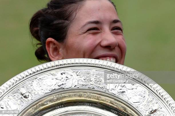 Spain's Garbine Muguruza holds The Venus Rosewater Dish as she celebrates beating US player Venus Williams to win the women's singles final on the...