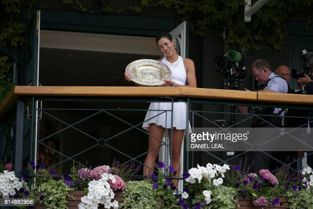 Spain's Garbine Muguruza holds up The Venus Rosewater Dish as she celebrates beating US player Venus Williams to win the women's singles final on the...