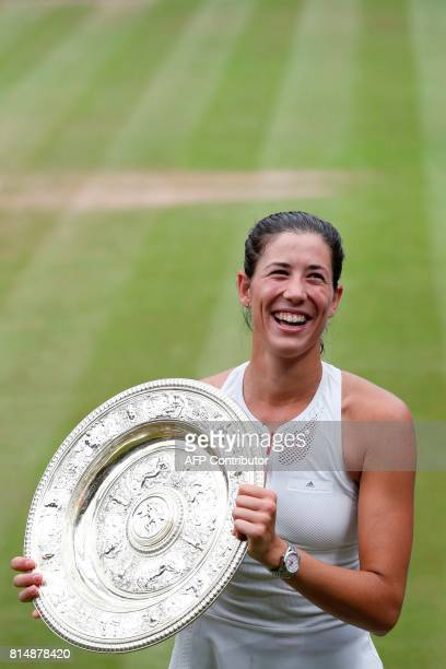 Spain's Garbine Muguruza laughs as she holds up The Venus Rosewater Dish as she celebrates beating US player Venus Williams to win the women's...