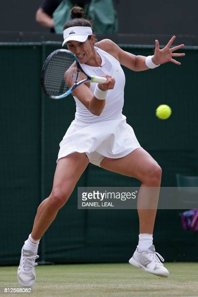 Spain's Garbine Muguruza returns against Russia's Svetlana Kuznetsova during their women's singles quarterfinal match on the eighth day of the 2017...