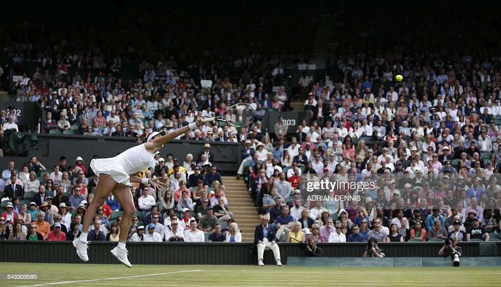 Spain's Garbine Muguruza serves against Italy's Camila Giorgi during their women's singles first round match on the first day of the 2016 Wimbledon Championships at The All England Lawn Tennis Club in Wimbledon, southwest London, on June 27, 2016. / AFP / ADRIAN
