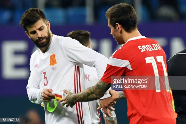 Spain's Gerard Pique and Russia's Fedor Smolov exchange their captain's armbands after an international friendly football match between Russia and...
