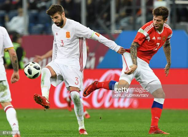 Spain's Gerard Pique and Russia's Fedor Smolov vie for the ball during an international friendly football match between Russia and Spain at the Saint...