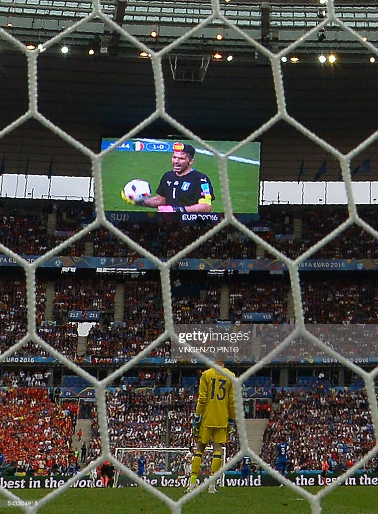 Spain's goalkeeper David De Gea (C) looks on as Italy's goalkeeper Gianluigi Buffon is displayed on a giant screen during the Euro 2016 round of 16 football match between Italy and Spain at the Stade de France stadium in Saint-Denis, near Paris, on June 27, 2016. / AFP / VINCENZO