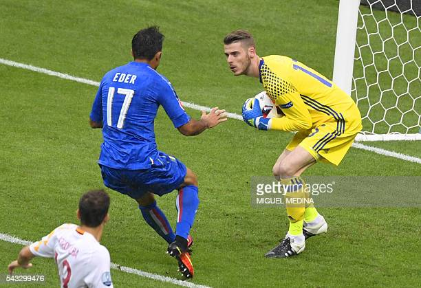 TOPSHOT Spain's goalkeeper David De Gea secures a ball in front of Italy's forward Citadin Martins Eder during Euro 2016 round of 16 football match...