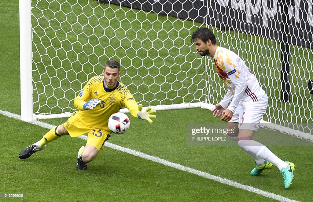 Spain's goalkeeper David De Gea (L) stops a ball beside Spain's defender Gerard Pique during Euro 2016 round of 16 football match between Italy and Spain at the Stade de France stadium in Saint-Denis, near Paris, on June 27, 2016. / AFP / PHILIPPE