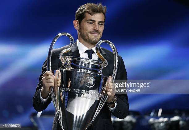 Spain's goalkeeper Iker Casillas arrives on stage with the European Champion Clubs' Cup during the draw for the 2014/2015 European Champions League...