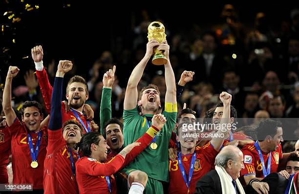Spain's goalkeeper Iker Casillas holds the FIFA World Cup tropfy after winning the 2010 World Cup football final by defeating The Netherlands during...