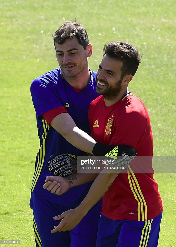 Spain's goalkeeper Iker Casillas (L) jokes with Spain's midfielder Cesc Fabregas during a training session at Saint Martin de Re's stadium on June 26, 2016, on the eve of their match against Italy during the Euro 2016 football tournament. / AFP / PIERRE