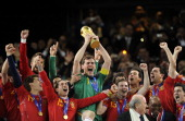 Spain's goalkeeper Iker Casillas raises the trophy handed to him by FIFA President Sepp Blatter and South Africa�s President Jacob Zuma as Spain's...