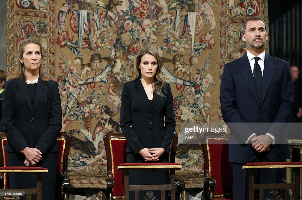 Spain's Infanta Elena, Spain's Princess Letizia and Spain's Crown Prince Felipe attend a memorial service for the victims the derailed train of Angrois, at the cathedral of Santiago de Compostela on July 29, 2013. The driver of a train that hurtled off the rails in Spain was charged on July 28 with 79 counts of reckless homicide and released on bail after being questioned by a judge.