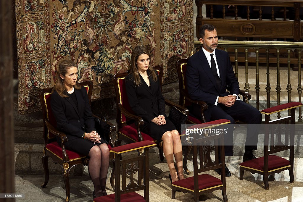 Spain's Infanta Elena, Spain's Princess Letizia and Spain's Crown Prince Felipe attend a memorial service for the victims the derailed train of Angrois, at the cathedral of Santiago de Compostela on July 29, 2013. The driver of a train that hurtled off the rails in Spain was charged on July 28 with 79 counts of reckless homicide and released on bail after being questioned by a judge. AFP PHOTO/ XUNTA/ XOAN CRESPO