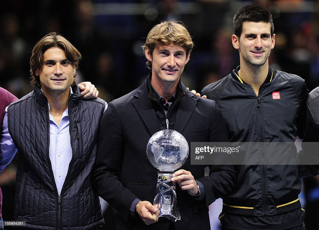 Spain's Juan Carlos Ferrero poses with a trophy presented to him to mark his retirement after 13 years on the ATP tour next to Serbia's Novak Djokovic (R) and Spain's David Ferrer (L) on the fifth day of the ATP World Tour Finals tennis tournament in London on November 9, 2012. Former world number one Juan Carlos Ferrero retired from professional tennis in October 2012 after a career in which he won 16 ATP tour singles titles including a grand slam. AFP PHOTO / GLYN KIRK