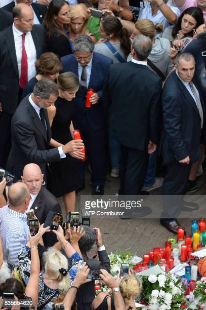 Spain's King Felipe VI and Spain's Queen Letizia display candles for the victims of the Barcelona attack on Las Ramblas boulevard in Barcelona on...