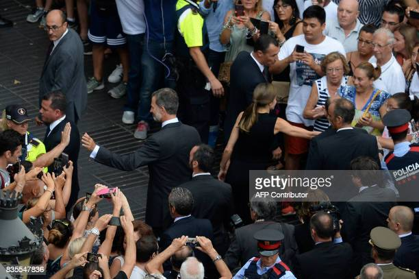 Spain's King Felipe VI and Spain's Queen Letizia greet people as they leave after paying tribute to the victims of the Barcelona attack on Las...