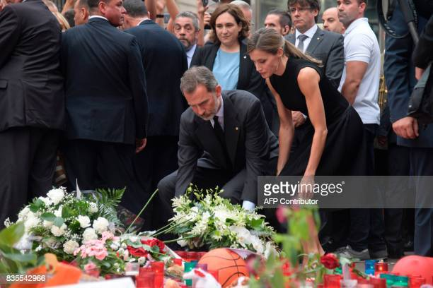 Spain's King Felipe VI and Spain's Queen Letizia lay a wreath of flowers for the victims of the Barcelona attack on Las Ramblas boulevard next to...
