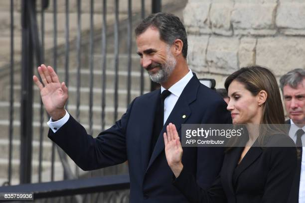 Spain's King Felipe VI and Spain's Queen Letizia wave as they leave after a mass to commemorate victims of two devastating terror attacks in...