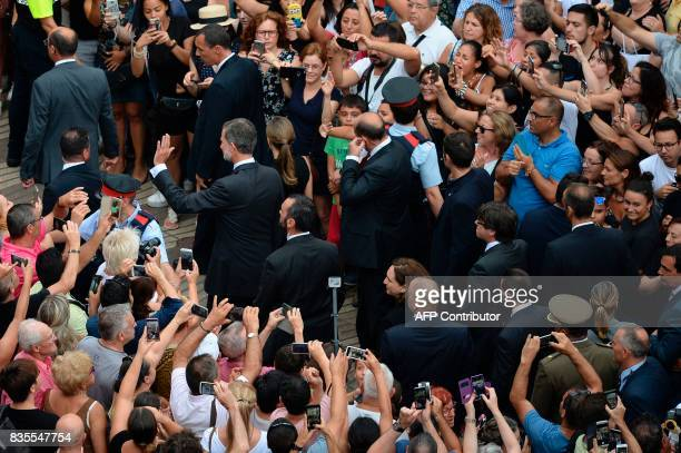 Spain's King Felipe VI and Spain's Queen Letizia wave as they leave after paying tribute to the victims of the Barcelona attack on Las Ramblas...