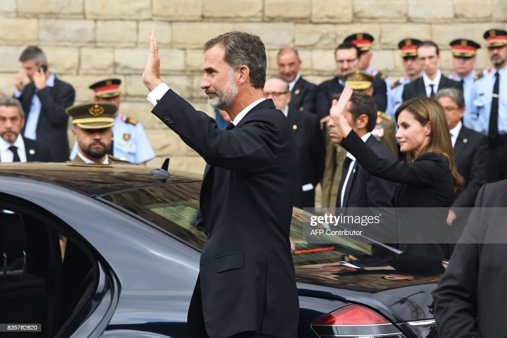 Spain's King Felipe VI and Spain's Queen Letizia wave as they leave the Sagrada Familia church after a mass to commemorate victims of two devastating terror attacks in Barcelona and Cambrils, in Barcelona on August 20, 2017. A grief-stricken Barcelona prepared today to commemorate victims of two devastating terror attacks at a mass in the city's Sagrada Familia church. As investigators scrambled to piece together the attacks which killed 14 people in all, Interior Minister Juan Ignacio Zoido said on August 19 the cell behind the carnage that also injured 120 and plunged the country into shock had been 'dismantled,' though local authorities took a more cautious tone. GUYOT
