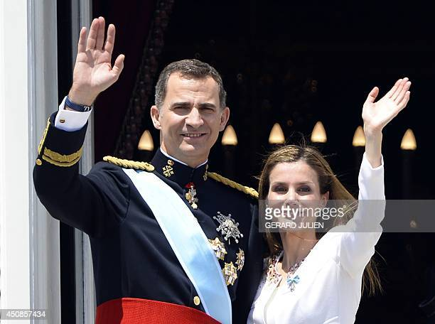 Spain's King Felipe VI and Spain's Queen Letizia wave on the balcony of the Palacio de Oriente or Royal Palace in Madrid on June 19 2014 following a...