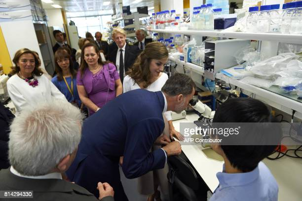Spain's King Felipe VI looks through a microscope in a laboratory during the visit to the Francis Crick Institute in central London on July 14 the...