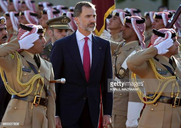 Spain's King Felipe VI review the honour guard during a welcome ceremony in the capital Amman on May 19 2017 / AFP PHOTO / Khalil MAZRAAWI