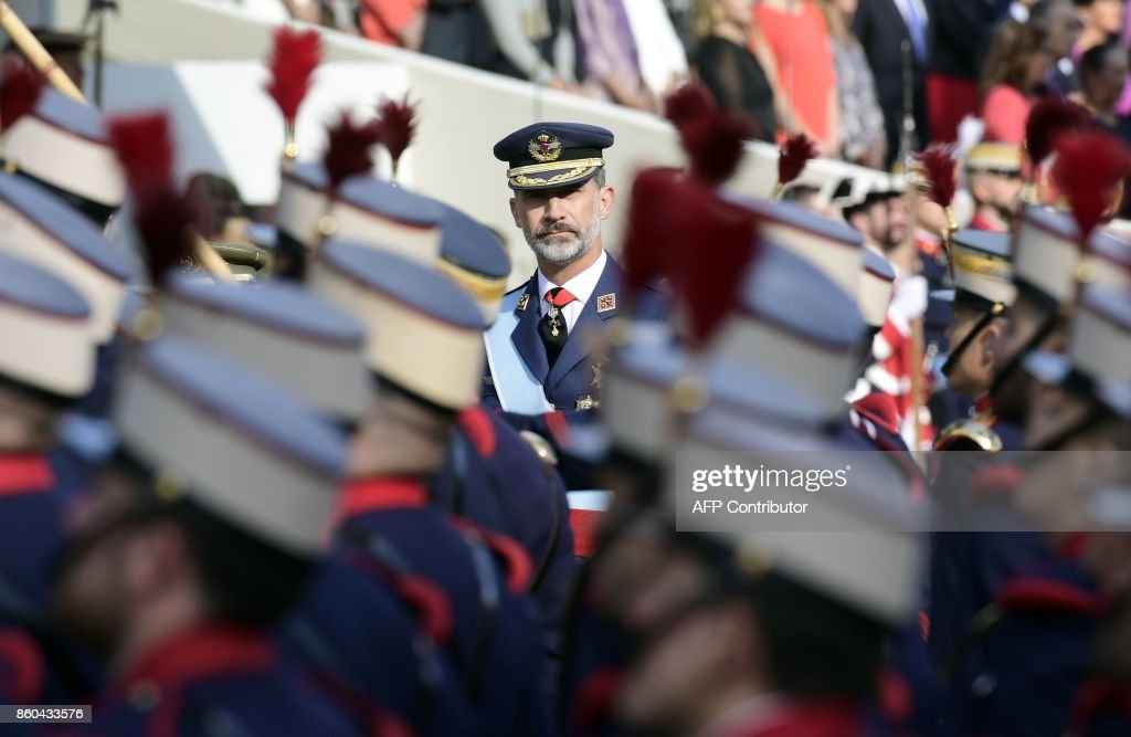 TOPSHOT - Spain's King Felipe VI reviews the troops during the Spanish National Day military parade in Madrid on October 12, 2017. Spain marks its national day today under high tension as the country reels from the biggest challenge to unity in a generation with its Catalan region threatening to break away. Prime Minister Mariano Rajoy and King Felipe VI attended the traditional military parade in central Madrid that marks October 12, the day that Christopher Columbus first arrived in the Americas in 1492 and a nationwide holiday. SORIANO