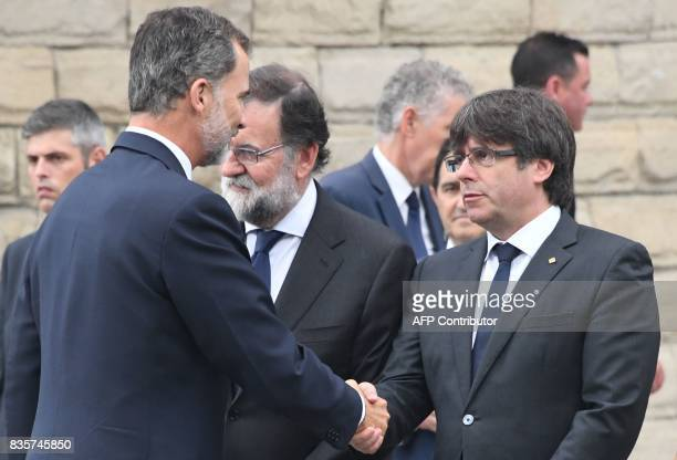 Spain's King Felipe VI shakes hands with President of Catalonia Carles Puigdemon upon his arrival for a mass to commemorate victims of two...