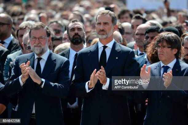 Spain's King Felipe VI Spanish Prime Minister Mariano Rajoy and President of Catalonia Carles Puigdemont applaud after observing a minute of silence...