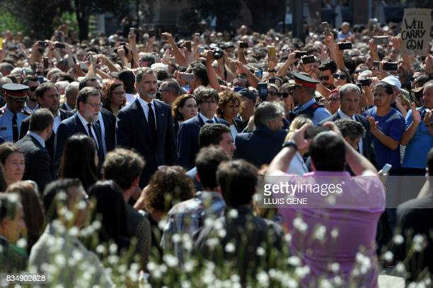 TOPSHOT Spain's King Felipe VI Spanish Prime Minister Mariano Rajoy and President of Catalonia Carles Puigdemont wait before observing a minute of...