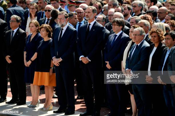 Spain's King Felipe VI Spanish Prime Minister Mariano Rajoy President of Catalonia Carles Puigdemont and officials observe a minute of silence for...