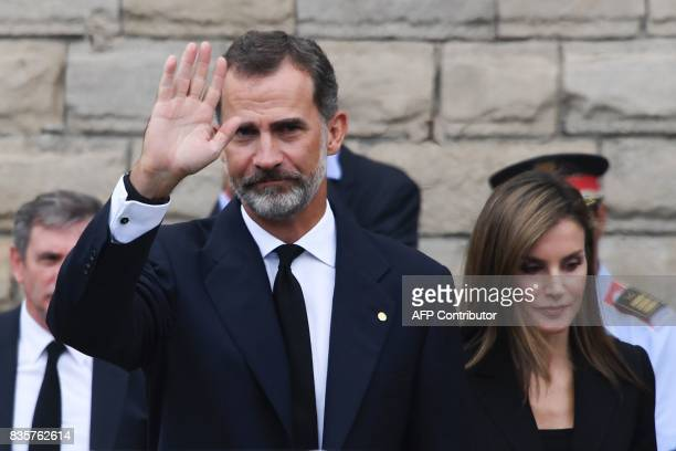Spain's King Felipe VI waves next to Spain's Queen Letizia as they leave the Sagrada Familia church after a mass to commemorate victims of two...