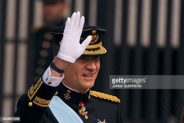 Spain's King Felipe VI waves on arrival at the Congress of Deputies Spain's lower House in Madrid on June 19 2014 for a swearing in ceremony of...