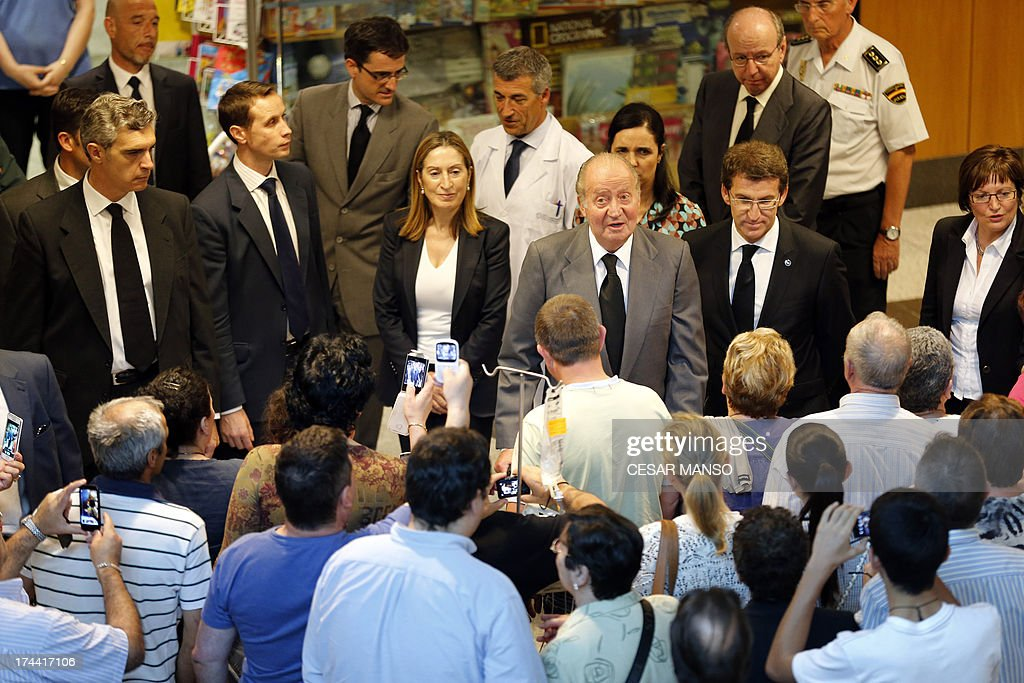 Spain's King Juan Carlos (3rd R), flanked by Galicia's regional President Alberto Nunez Feijoo (2nd R) and Spanish Minister of Public Works and Transport Ana Pastor (3rd L), leaves the University Clinical Hospital of Santiago de Compostela on July 25, 2013. A train hurtled off the tracks on July 24 in northwest Spain killing at least 80 passengers and injuring more than 140, an official said today, the country's deadliest rail disaster in more than 40 years.