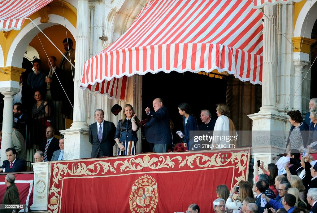 Spain's King Juan Carlos I (C) throws back Spanish matador Enrique Ponce's montera (Matador's hat) as he stands between Elena de borbon (CL) and Victoria Federica de Marichalar y Borbon (CR) during a bullfight at the Maestranza bullring, in Sevilla on April 9, 2016. / AFP / CRISTINA