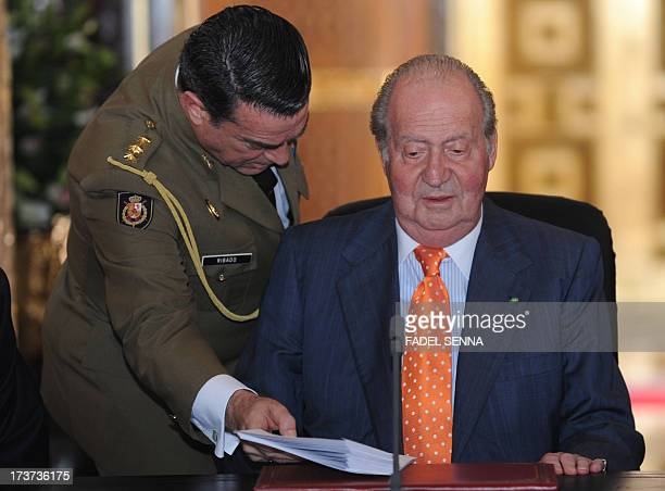 Spain's King Juan Carlos is presented documents as he meets with Moroccan Minister of Higher education on July 172013 in the Moroccan city of Rabat...