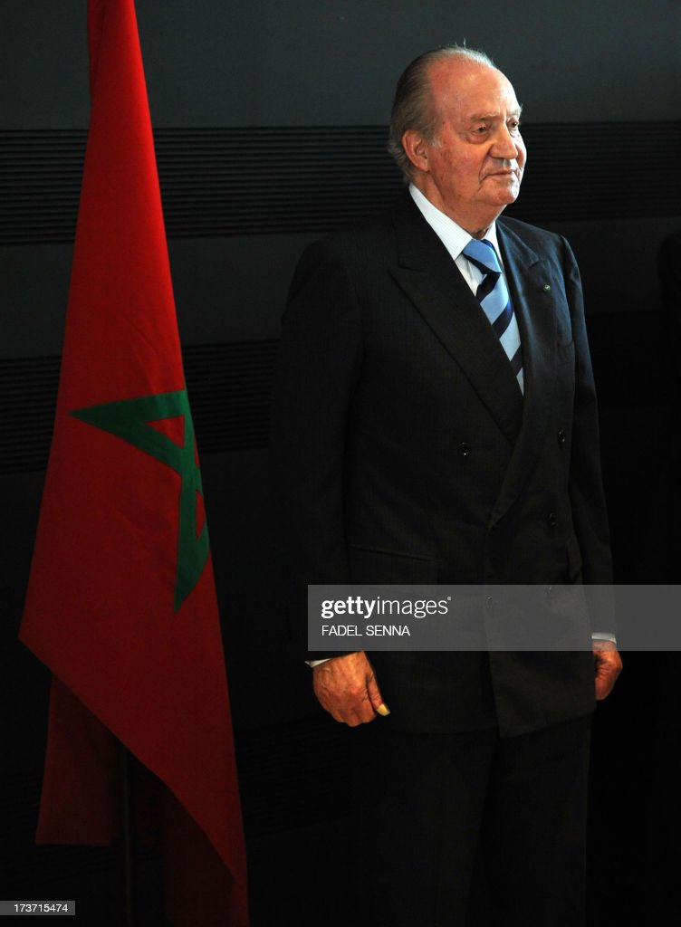 Spain's King Juan Carlos stands in front of a Moroccan flag during a conference in the capital Rabat on July 16, 2013. King Juan Carlos is on a four-day visit to Morocco, at the invitation of King Mohammed VI, his first outside of Spain since he had back surgery in March, and is expected to reflect the close diplomatic ties between Rabat and Madrid.
