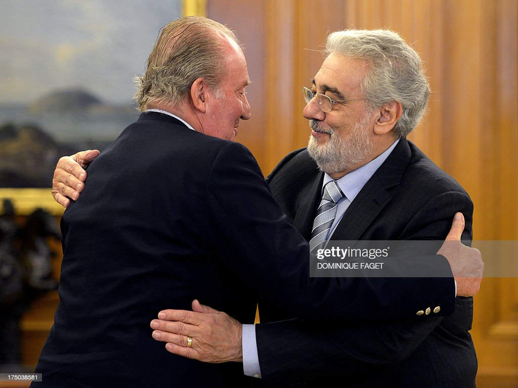 Spain's King Juan Carlos (L) welcomes Spanish tenor Placido Domingo during a meeting at the Zarzuela Palace in Madrid on July 29, 2013. Domingo is feeling well after a treatment for a blockage in his lung two weeks ago. The 72-year-old, popularly known for his 'Three Tenors' performances with Jose Carreras and the late Luciano Pavarotti, was admitted to hospital in the Spanish capital on July 8, 2013 and treated for a pulmonary embolism.