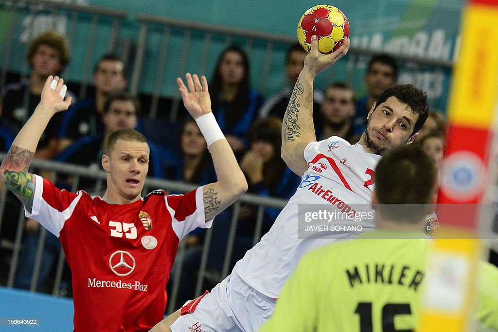 Spain's left back Alberto Enterrios (R) shoots past Hungary's pivot Szabolcs Zubai during the 23rd Men's Handball World Championships preliminary round Group D match Hungary vs Spain at the Caja Magica in Madrid on January 17, 2013.