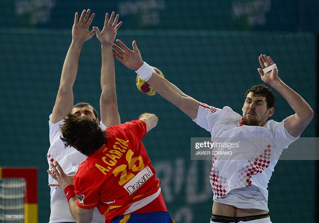 Spain's left back Antonio Jesus Garcia (C) shoots in front of Croatia's pivot Zeljko Musa (L) and Croatia's left back Jakov Gojun (R) during the 23rd Men's Handball World Championships preliminary round Group D match Spain vs Croatia at the Caja Magica in Madrid on January 19, 2013.