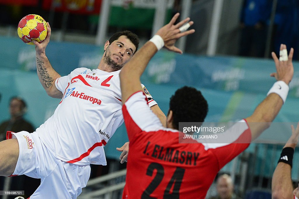 Spain's leftback Alberto Enterrios (L) shoots in front of Egypt's pivot Ibrahim Mohamed (R) during the 23rd Men's Handball World Championships preliminary round Group D match Egypt vs Spain at the Caja Magica in Madrid on January 14, 2013.