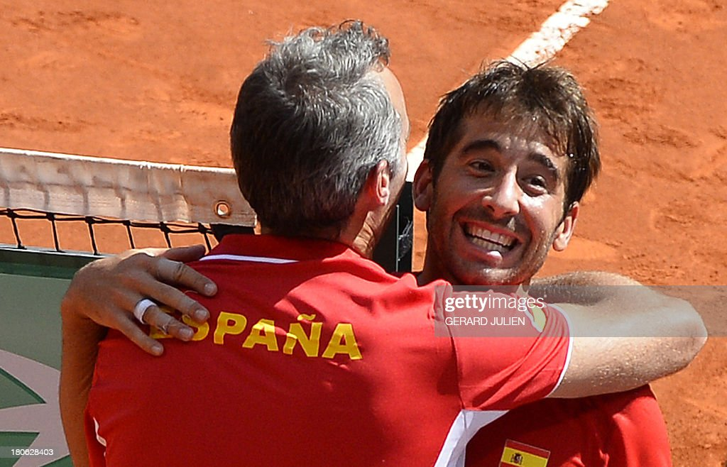 Spain's Marc Lopez (R) is congratulated by Spain's captain Alex Corretja after defeating Ukraine's Denys Molchanov during the Davis Cup World Group Play-offs 2013 at the Caja Magica sports complex in Madrid on September 15, 2013. Lopez won 6-3, 6-3. AFP PHOTO/ GERARD JULIEN / AFP / GERARD JULIEN