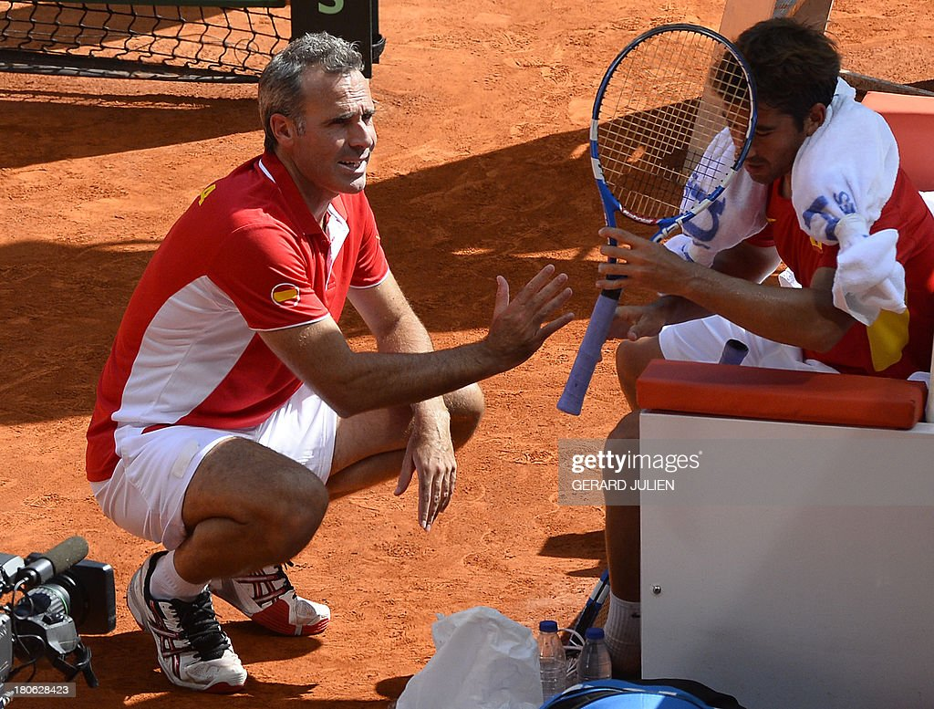 Spain's Marc Lopez (R) listens to Spain's captain Alex Corretja during the Davis Cup World Group Play-offs 2013 against Ukraine's Denys Molchanov at the Caja Magica sports complex in Madrid on September 15, 2013. Lopez won 6-3, 6-3.
